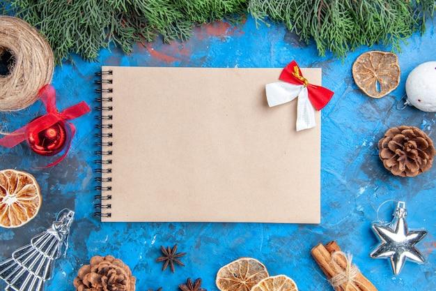 상위 뷰 소나무 나뭇가지 짚 실 계피 스틱 말린 레몬 조각 아니스 씨앗 파란색-빨간색 표면에 작은 활이 있는 노트북