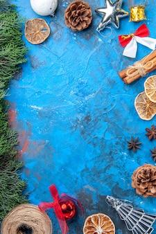 Vista dall'alto rami di pino filo di paglia bastoncini di cannella fette di limone essiccate semi di anice albero di natale colorato giocattoli su superficie blu-rossa