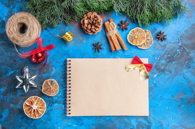 Top view pine tree branches straw thread cinnamon sticks dried lemon slices anise seeds a notebook on blue-red background
