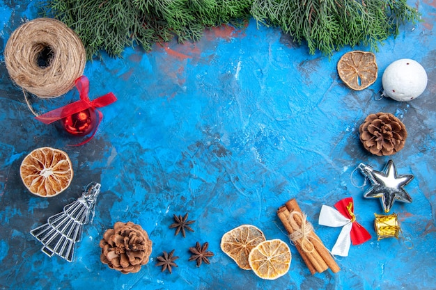 Top view pine tree branches straw thread cinnamon sticks dried lemon slices anise seeds xmas tree toys on blue-red surface
