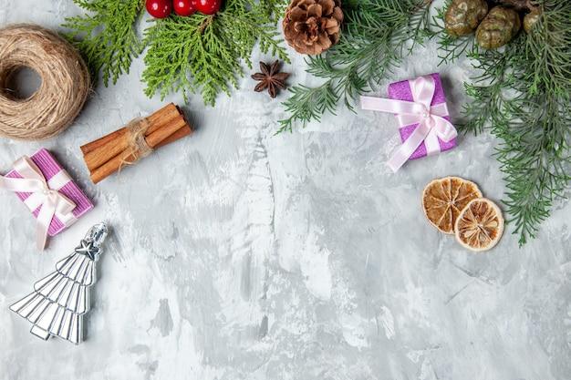 Vista dall'alto rami di pino filo di paglia bastoncini di cannella piccolo regalo su superficie grigia
