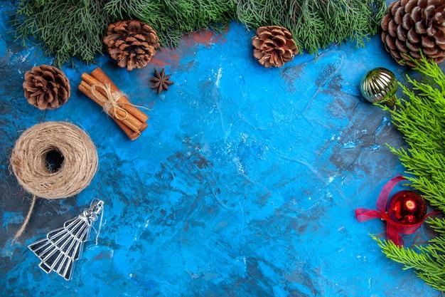 Vista dall'alto rami di pino filo di paglia bastoncini di cannella albero di natale giocattoli su sfondo blu-rosso