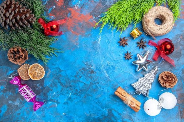 Top view pine tree branches straw thread xmas tree toys anise seeds cinnamon sticks dried lemon slices on blue-red background with copy place