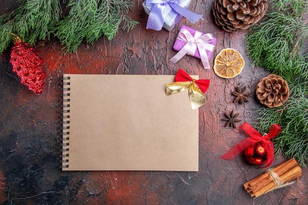 Vista dall'alto rami di pino con coni anice cannella dettagli di natale un quaderno su superficie rosso scuro