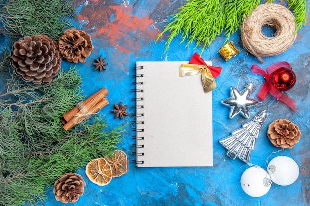 Vista dall'alto rami di pino con coni bastoncini di cannella semi di anice fette di limone essiccate filo di paglia albero di natale giocattoli un quaderno su superficie blu-rossa