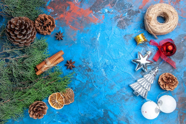 Top view pine tree branches with cones cinnamon sticks anise seeds dried lemon slices and vertical row straw thread xmas tree toys on blue-red background with copy place