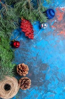 Вид сверху сосновые ветки с шишками и красочные рождественские игрушки соломенной нитью на сине-красной поверхности