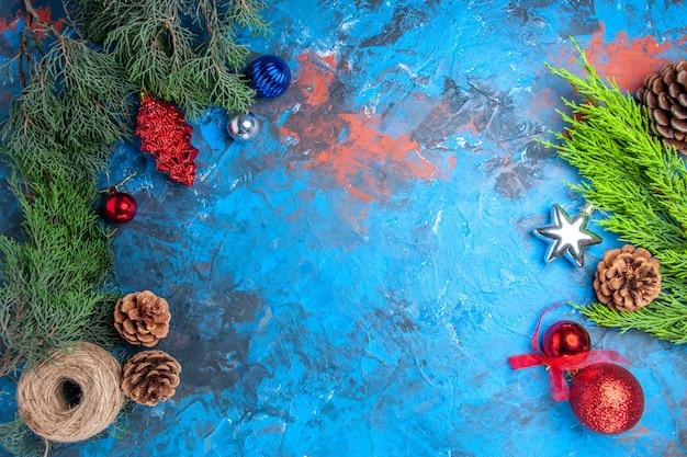 Vista dall'alto rami di pino con pigne e colorati giocattoli di albero di natale filo di paglia su superficie blu-rossared