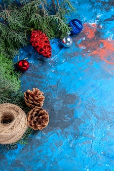 Top view pine tree branches with pinecones and colorful xmas tree toys straw thread on blue-red surface