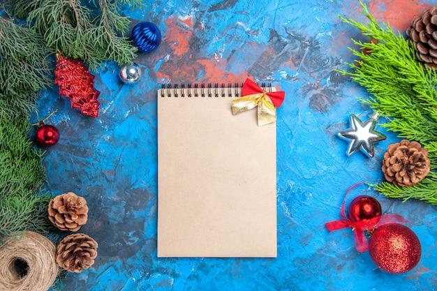 Vista dall'alto rami di pino con pigne e colorati giocattoli di albero di natale infilare un taccuino su sfondo blu-rosso