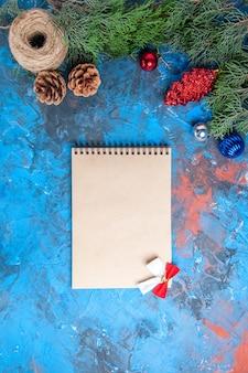 Vista dall'alto rami di pino con pigne e coloratissimi giocattoli di albero di natale quaderno di filo di paglia con fiocco su sfondo blu-rosso