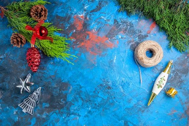 Top view pine tree branches with pinecones hanging ornaments straw thread on blue-red surface