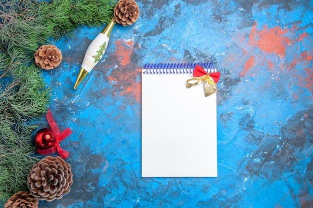 Vista dall'alto rami di pino con pigne un quaderno su superficie blu-rossa