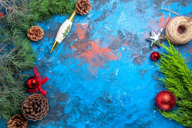파란색-빨간색 배경에 솔방울이 있는 상위 뷰 소나무 가지