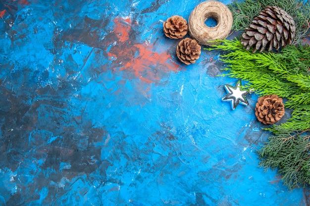파란색-빨간색 표면에 솔방울 짚 스레드 스타 크리스마스 펜던트가 있는 상위 뷰 소나무 가지