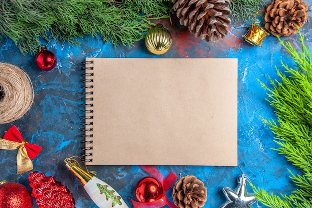 Vista dall'alto rami di pino con pigne filo di paglia ornamenti appesi di natale un quaderno su superficie blu-rossa