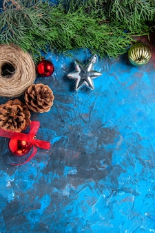 Top view pine tree branches with pinecones straw thread xmas toys on blue-red surface