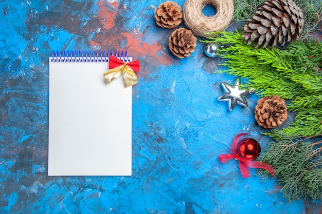 Top view pine tree branches with pinecones straw thread xmas toys a notebook on blue-red background free space