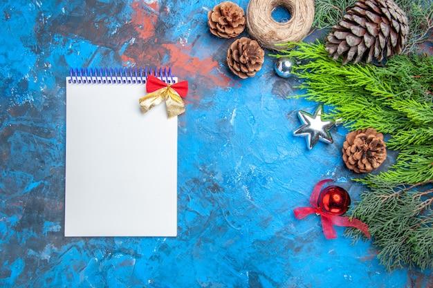 Vista dall'alto rami di pino con pigne filo di paglia giocattoli natalizi un quaderno su superficie blu-rossa