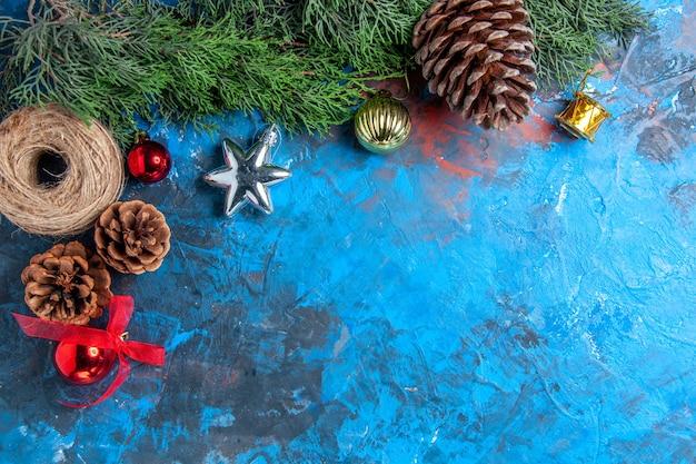 파란색-빨간색 표면에 솔방울 짚으로 만든 크리스마스 장난감이 있는 상위 뷰 소나무 가지