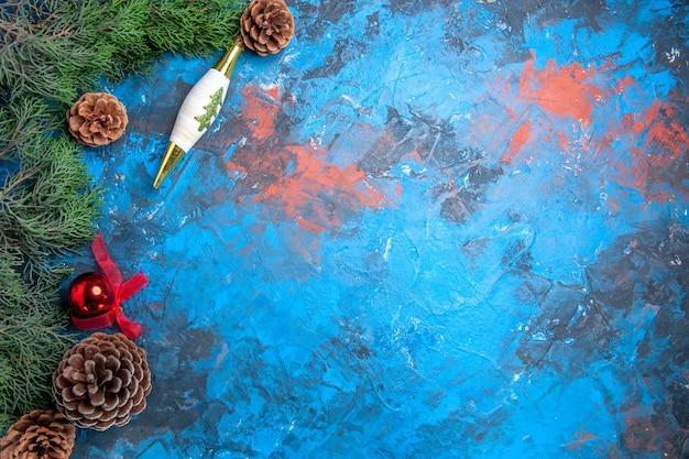 Vista dall'alto rami di pino con pigne giocattoli di natale su superficie blu-rossa