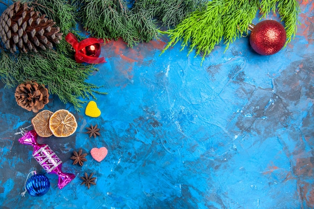 Top view pine tree branches xmas tree toys anise seeds dried lemon slices heart shaped candies on blue-red surface