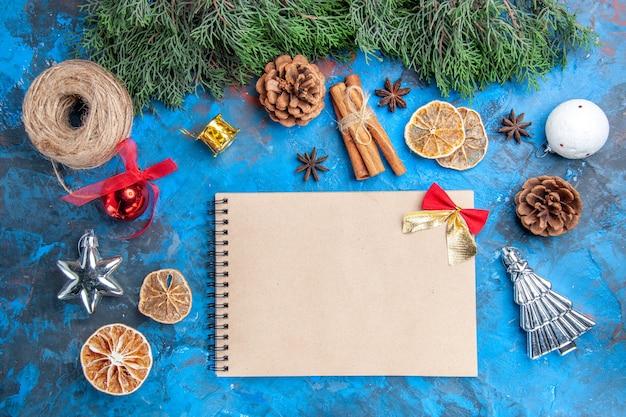 상위 뷰 소나무 나뭇가지 크리스마스 트리 장난감 짚 실 계피 스틱 말린 레몬 조각 아니스 씨앗 파란색-빨간색 배경에 노트북