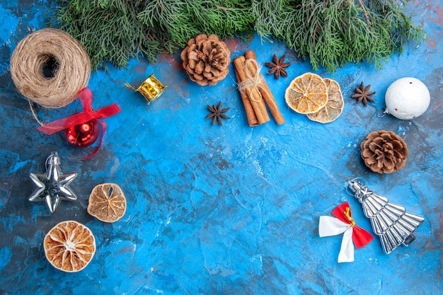 상위 뷰 소나무 나뭇가지 크리스마스 트리 장난감 빨대 실 계피 스틱 말린 레몬 조각 아니스 씨앗 파란색-빨간색 배경 무료 장소