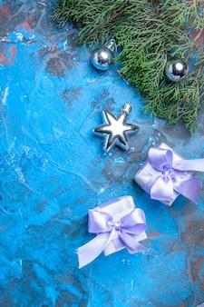 Vista dall'alto rami di pino albero di natale giocattoli regali di natale su superficie blu-rossa