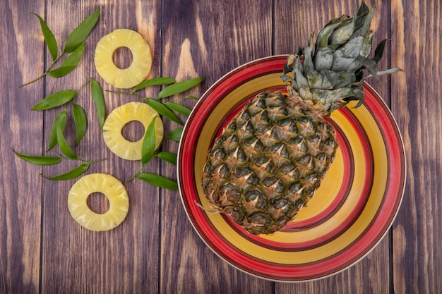 Top view of pineapple in bowl with pineapple slices and leaves on wooden surface