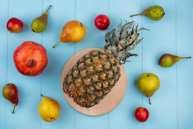 Top view of pineapple on cutting board and pattern of fruits as pomegranate peach plum on blue surface