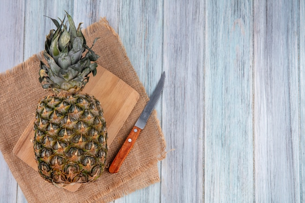 Top view of pineapple on cutting board with knife on sackcloth and wooden surface