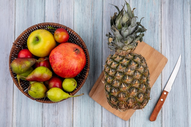 Top view of pineapple on cutting board with pomegranate peach apple plum in basket with knife on wooden surface