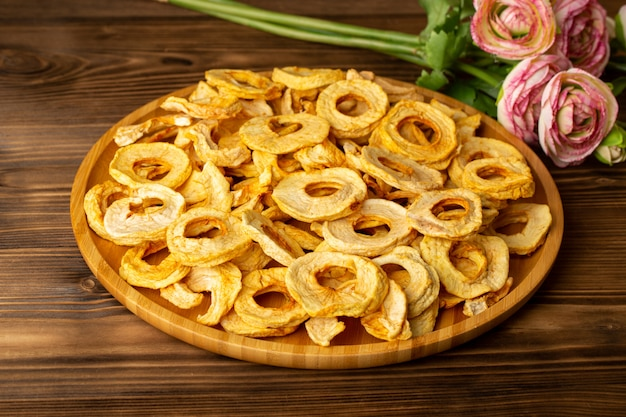 Una vista dall'alto ananas essiccato anelli all'interno della scrivania frutta secca gusto unico insieme a fiori rosa sulla scrivania in legno marrone frutti esotici secchi