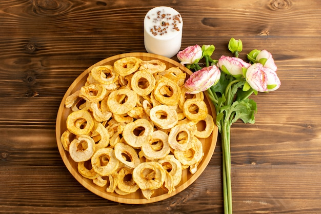 A top view pineapple dried rings inside plate dried fruits sour tasty unique taste along with pink flowers on the brown wooden desk fruits exotic dry