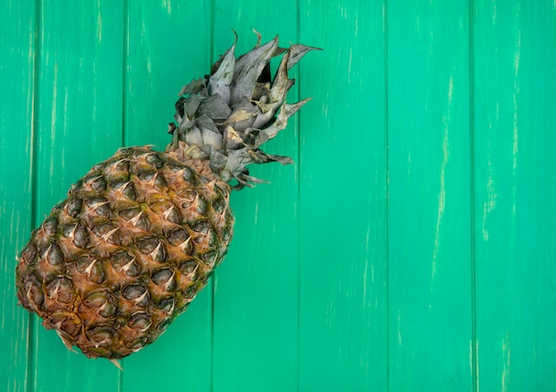 Top view of pineapple on green surface