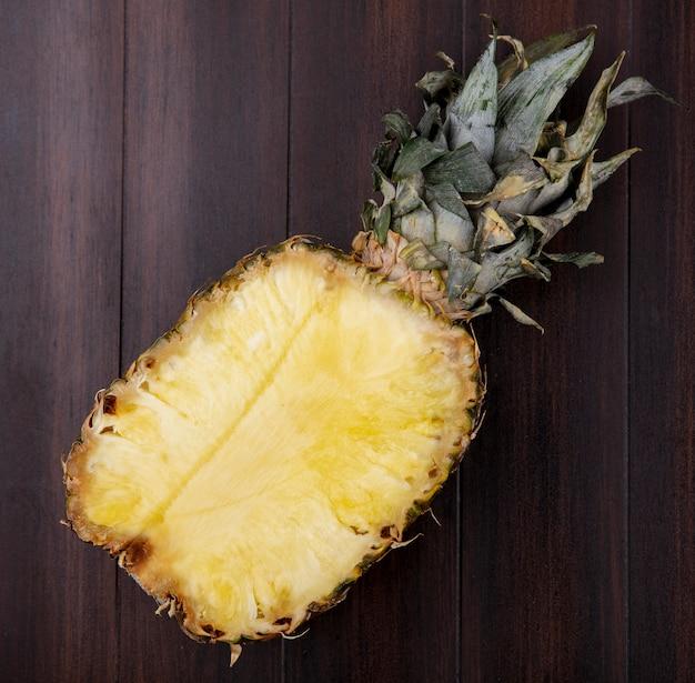 Vista superiore dell'ananas mezzo su superficie di legno