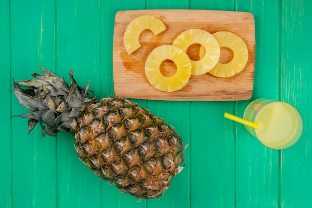 Top view of pineapple juice with pineapple slices on cutting board and pineapple on green surface