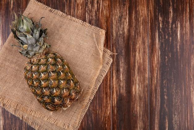 Vista dall'alto di ananas su tela di sacco e superficie in legno