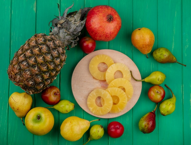 Top view of pineapple slices on cutting board and pineapple pomegranate peach plum apple on green surface