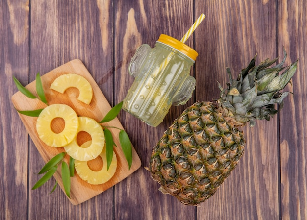Top view of pineapple slices on cutting board with pineapple juice and pineapple on wooden surface