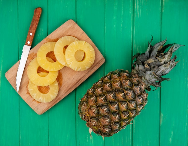 Top view of pineapple slices and knife on cutting board with whole one on green surface