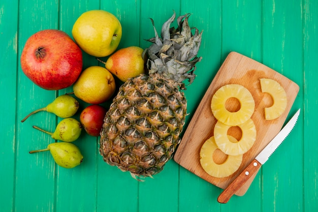 Top view of pineapple slices with knife on cutting board and pineapple pomegranate peach plum on green surface