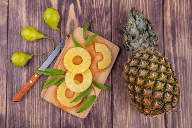 Top view of pineapple slices with leaves on cutting board and pineapple peach with knife on wooden surface