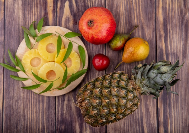 Top view of pineapple slices with leaves on cutting board and pineapple pomegranate peach plum on wooden surface