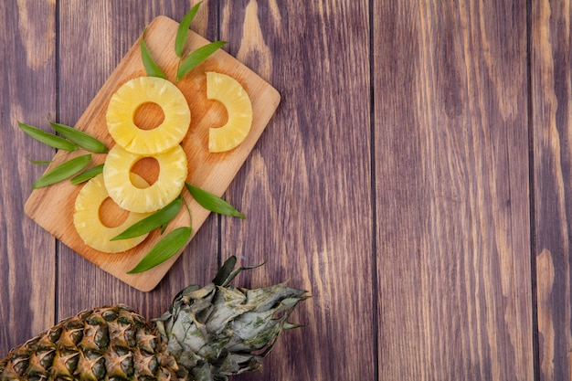 Top view of pineapple and slices with leaves on cutting board and wooden surface