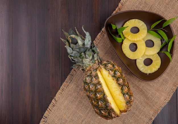 Top view of pineapple with one piece cut out from whole fruit and bowl of pineapple slices on sackcloth and wooden surface