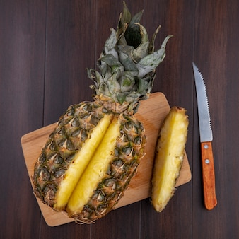 Top view of pineapple with one piece cut out from whole fruit on cutting board with knife on wooden surface