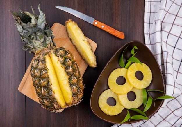 Top view of pineapple with one piece cut out from whole fruit on cutting board with pineapple slices and knife on wooden surface
