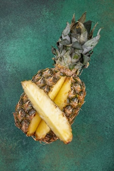 Top view of pineapple with one piece cut out from whole fruit on green surface